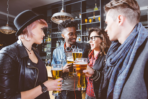 Multi Ethnic Friends Drinking Beer In A Pub Stock Photo - Download Image Now