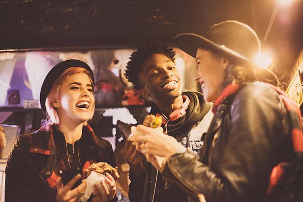 multi ethnic friends eating burgers in pub - streetfood stock-fotos und bilder