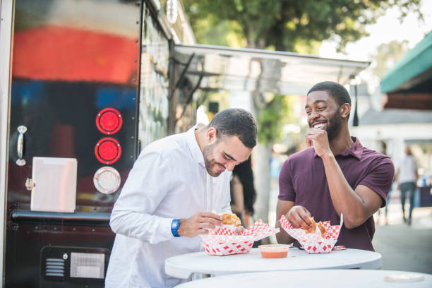 Multi Ethnic Friends Eating from the Food Trucks Armenian young man and African American young man eat food at a stand up table next to the food truck. Their food baskets are lined with red and white checkered paper liners. They laugh and share a good time together. armenian ethnicity stock pictures, royalty-free photos & images