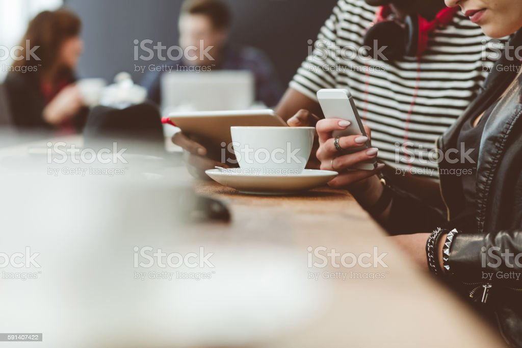 Multi ethnic friends using technologies in a coffee shop Afro american guy and his girlfriend sitting at the table in a coffee shop, man using digital tablet and women smart phone. Close up of hands, unrecognizable people. Adult Stock Photo