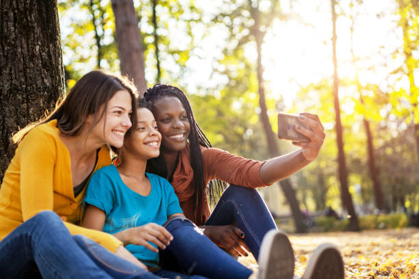 Multi ethnic friends with child taking selfie Multi ethnic friends with child taking selfie gay person stock pictures, royalty-free photos & images