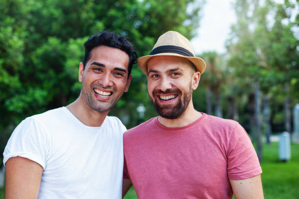 Multi ethnic gay couple hugging Two young man looking at the camera and smiling together in the park gay man stock pictures, royalty-free photos & images