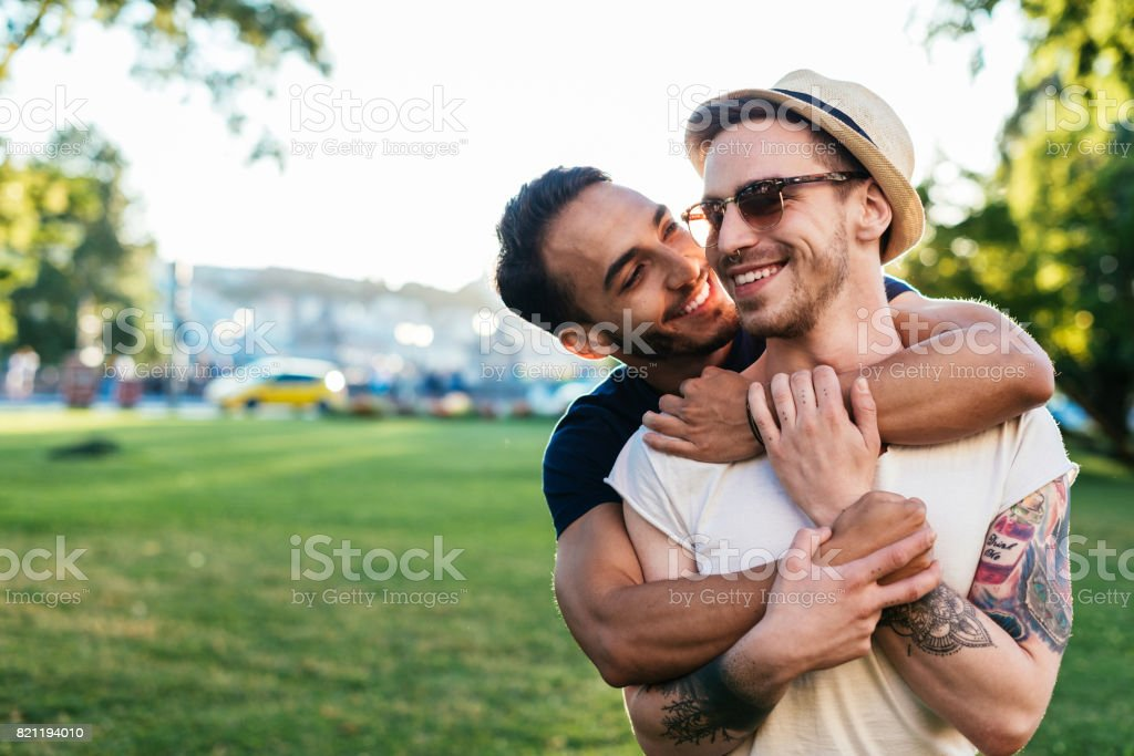 Multi ethnic gay couple hugging stock photo