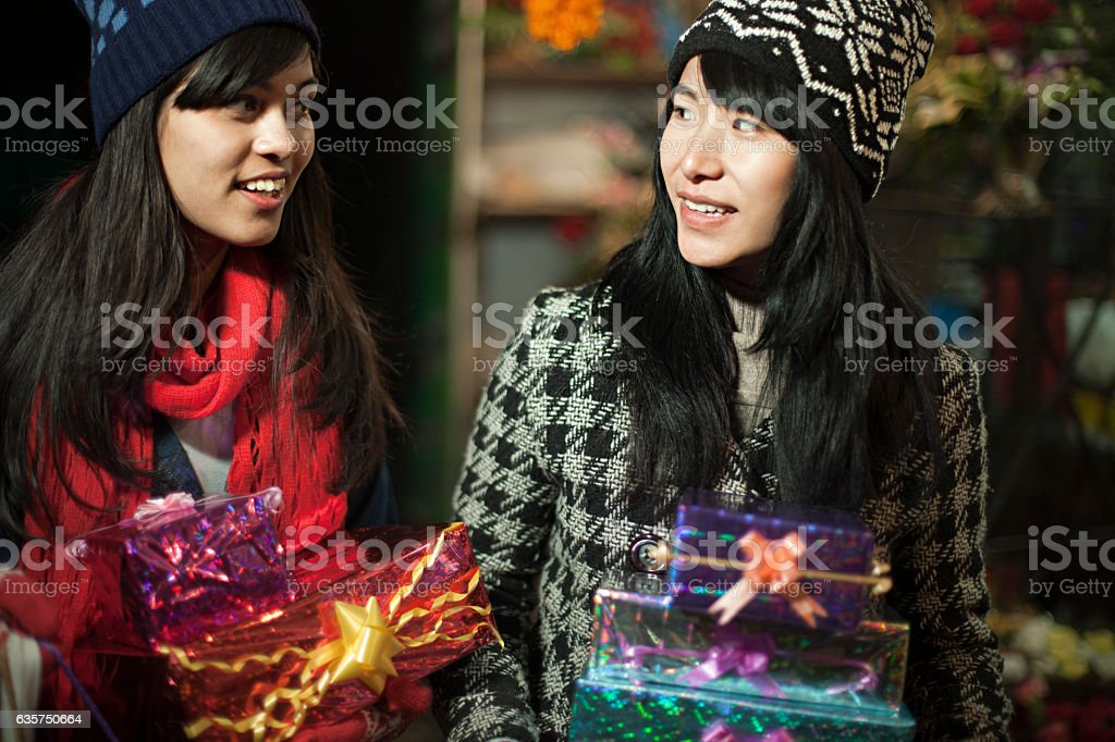 Multi Ethnic Girls In Market Carrying Gifts Stock Photo