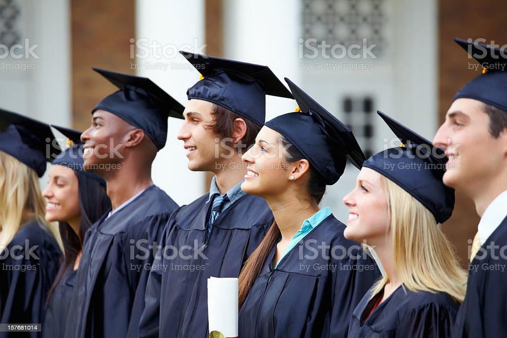 Multi ethnic graduation students smiling and looking away royalty-free stock photo