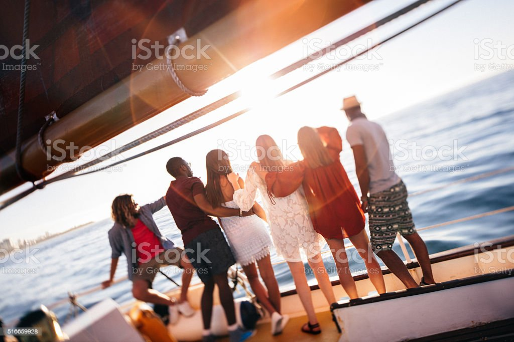 Multi ethnic group  friends looking at horizon from a yacht stock photo