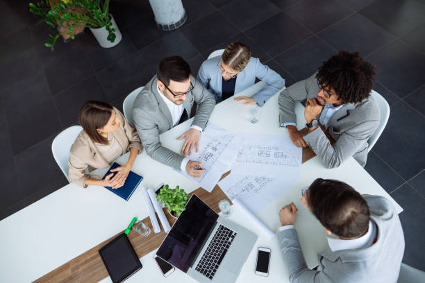Multi ethnic group of architects working on plans in board room stock photo