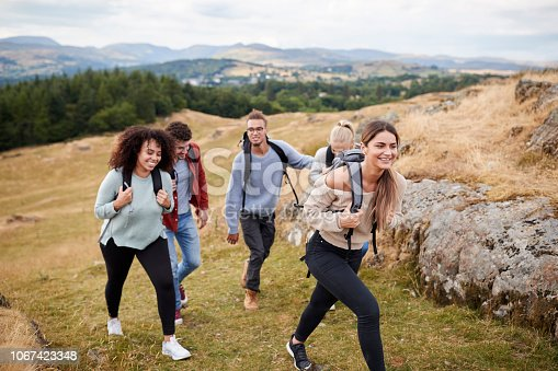 1051098428istockphoto Multi ethnic group of five young adult friends hiking across a field uphill towards the summit, close up 1067423348