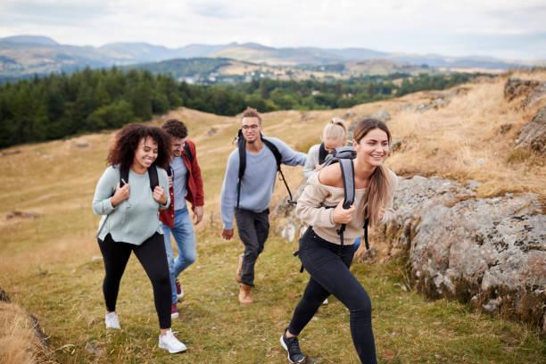 multi ethnic group of five young adult friends hiking across a field uphill towards the summit, close up - занятия на открытом воздухе стоковые фото и изображения