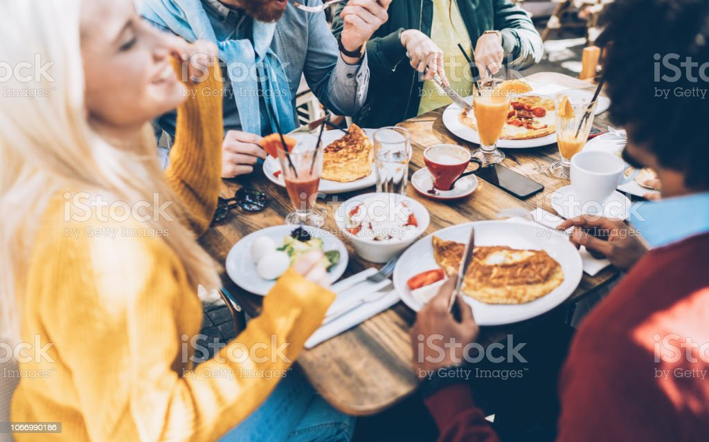 Multi ethnic group of friends eating lunch in a restaurant stock photo