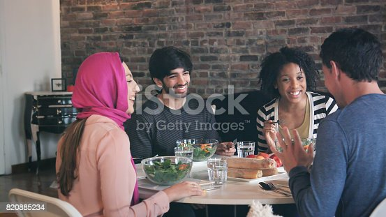 istock Multi Ethnic Group of Friends Enjoy Meal Together 820885234