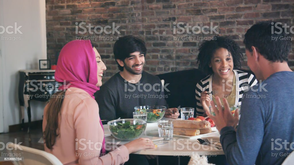 Multi Ethnic Group of Friends Enjoy Meal Together stock photo