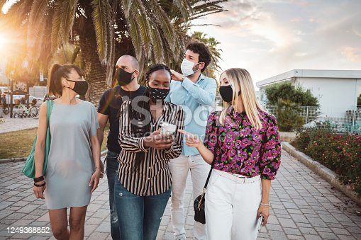 Multi ethnic group of friends meeting in the city wearing protective face masks having fun together after the lockdown which last for a couple of months.