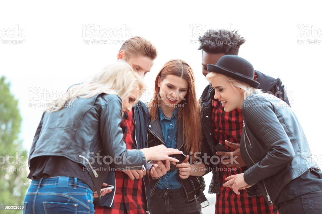 Multi ethnic group of friends using mobiles outdoors Multi ethnic group of happy young people using smart phones outdoors. 20-29 Years Stock Photo