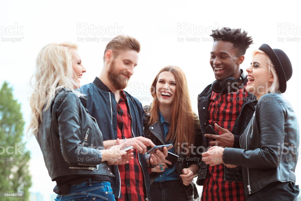 Multi ethnic group of friends using mobiles outdoors Multi ethnic group of happy young people using smart phone outdoors. 20-29 Years Stock Photo