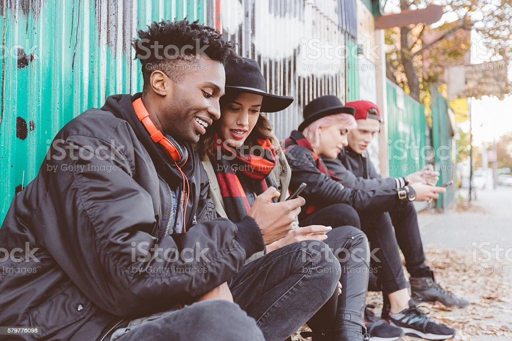 Multi ethnic group of hipsters outdoors usping phones stock photo