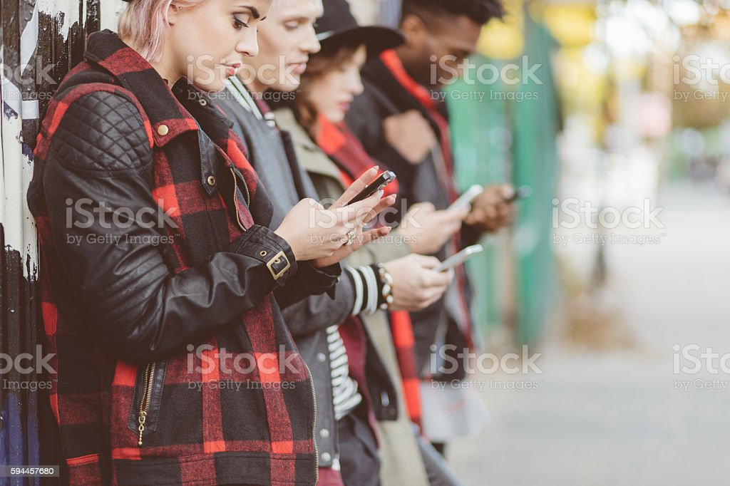Multi ethnic group of hipsters using mobiles outdoor Multi ethnic group of alternative friends using smart phones outdoors on city street. 20-29 Years Stock Photo