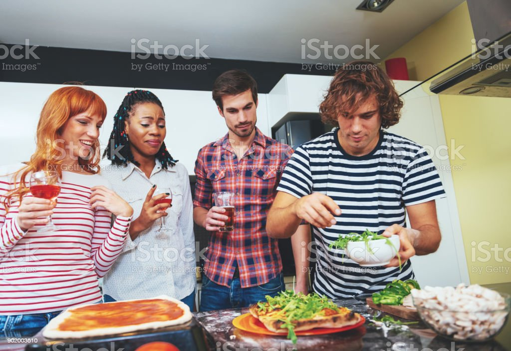 Multi ethnic group of people cooking dinner together stock photo