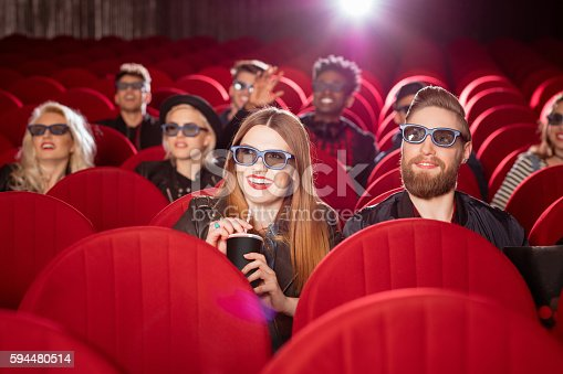istock Multi ethnic group of people in the 3D movie theater 594480514