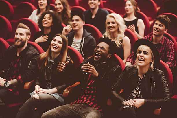 Multi ethnic group of people in the movie theater Multi ethnic group of young people in the cinema or theater, watching, laughing.  performance stock pictures, royalty-free photos & images