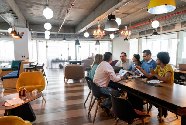 Multi ethnic group of professionals at a coworking office in a meeting discussing something Multi ethnic group of professionals at a coworking office in a meeting discussing something looking focused coworking stock pictures, royalty-free photos & images