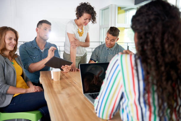 Multi ethnic group of succesful creative business people using a laptop during candid meeting stock photo