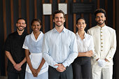 Multi ethnic group of workers at a luxury hotel all looking at camera smiling  very happy