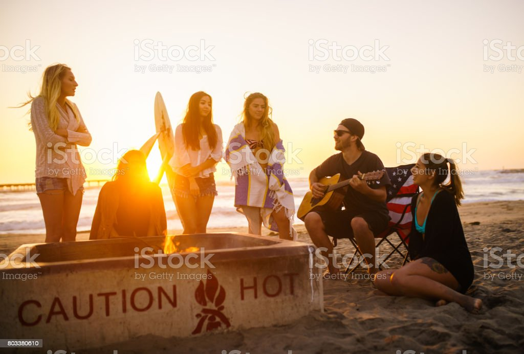 Multi ethnic group of young people, spending time watching sunset at the beach in San Diego, playing guitar and warming themselves by the fire stock photo