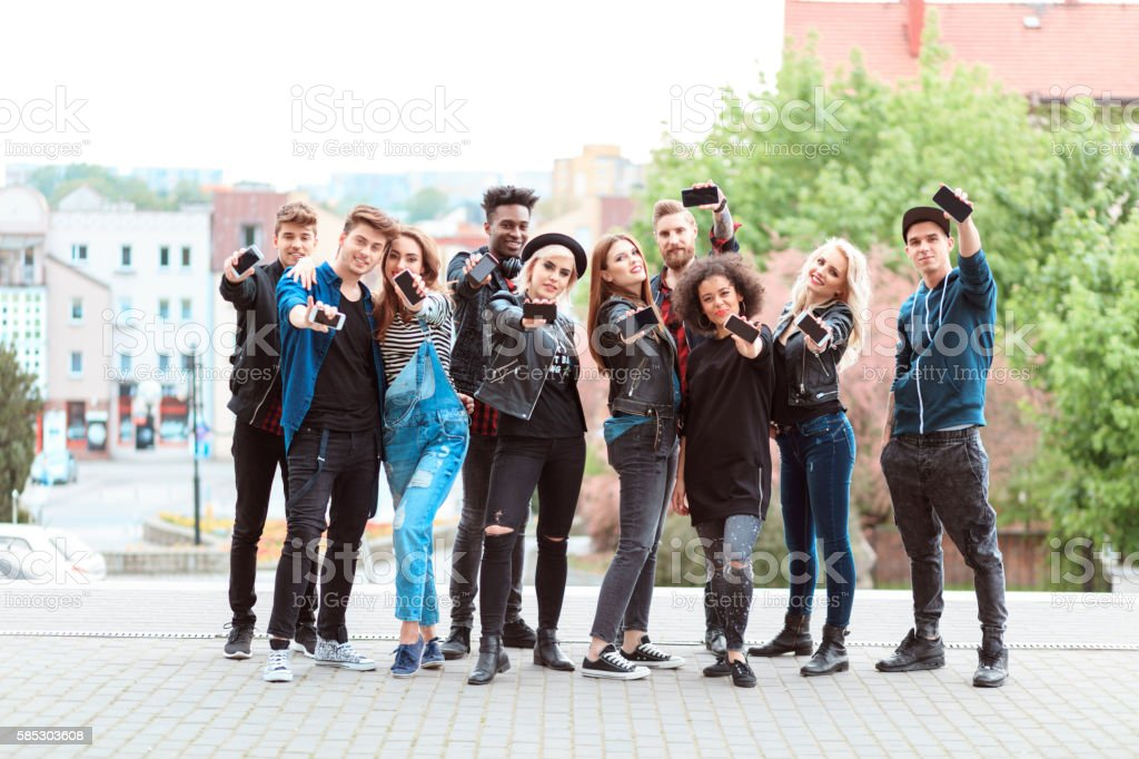 Multi ethnic group of young people with mobile phones Multi ethnic group of young people holding smart phones in hands in the city outdoors, smiling at camera. 20-29 Years Stock Photo