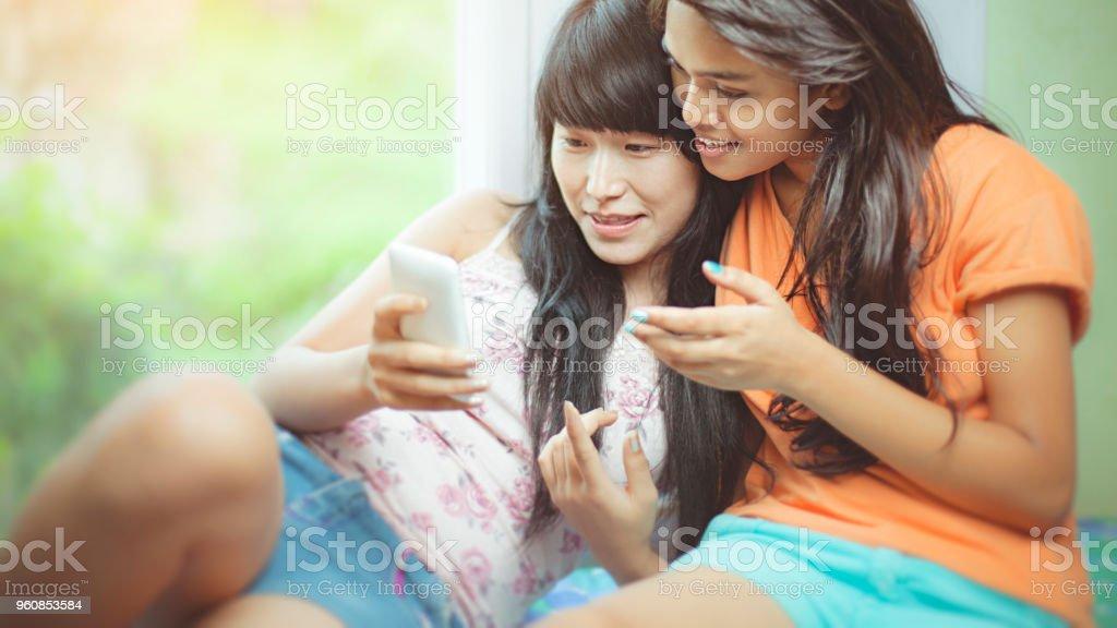 Multi ethnic happy female friends at home. stock photo