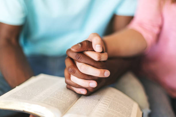 Multi Ethnic Heterosexual Generation Z Couple Holding Hands and Studying the Bible Together stock photo