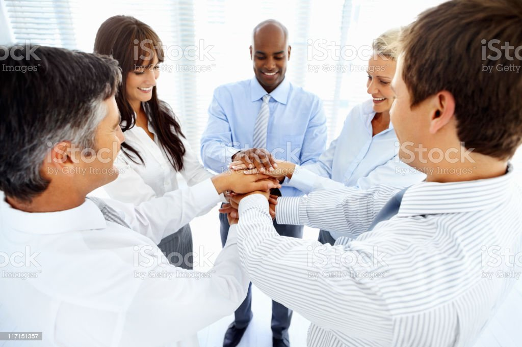 Multi ethnic professionals with hands over each other in unity royalty-free stock photo