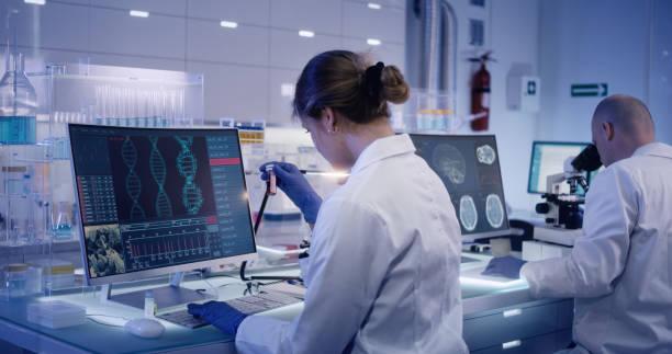 equipo de investigación multiétnico que estudia mutaciones de adn. doctora en primer plano - adn fotografías e imágenes de stock