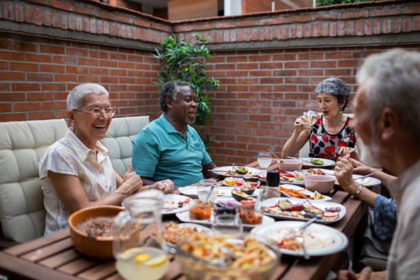 Multi Ethnic Senior Couple Enjoying In Vegan BBQ Dinner With Friends stock photo
