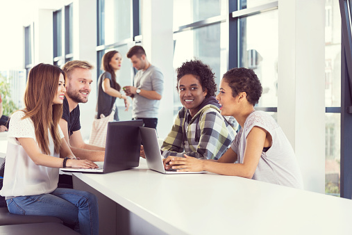 Multi Ethnic Students Working Together On Laptops At The University Stock Photo - Download Image Now