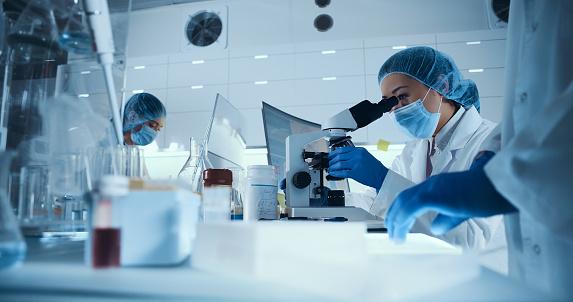 Multi ethnic team working with biohazardous samples. Asian female doctor using microscope