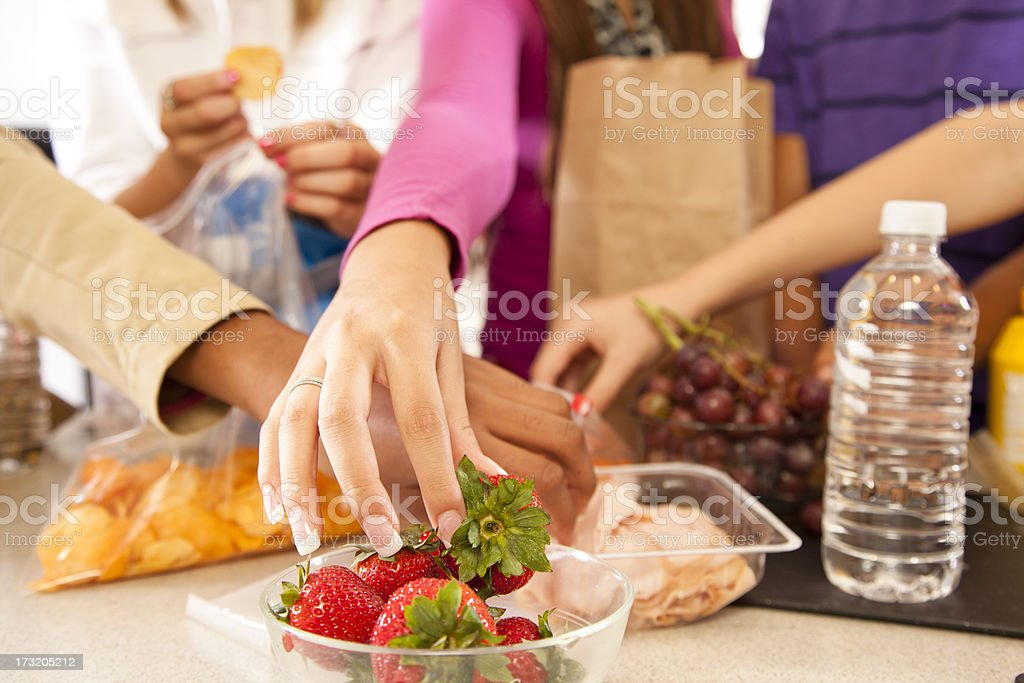 Multi ethnic teens in kitchen making school lunches. stock photo