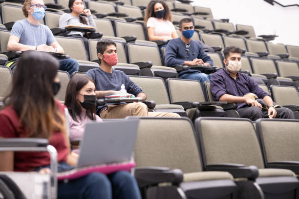 Multi ethnic university students in lecture hall stock photo