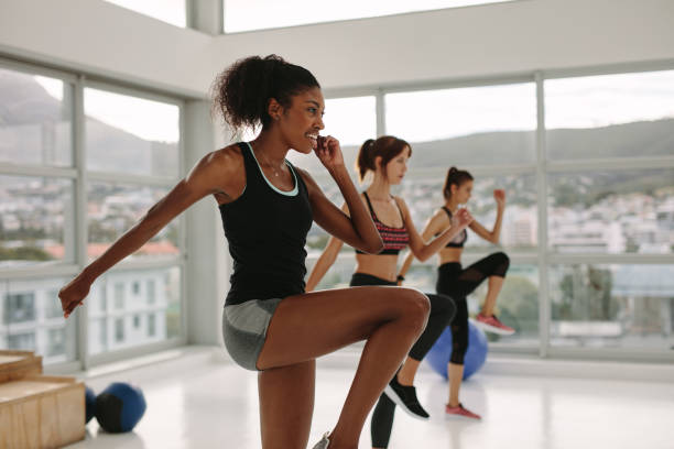 multi ethnic  women exercises in gym class - aerobics stock photos and pictures