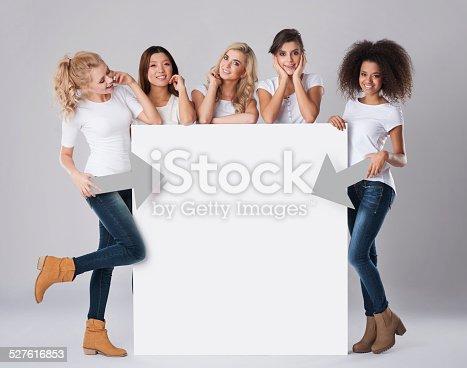 istock Multi ethnic women with empty billboard 527616853
