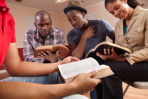 multi ethnic young adults in a bible study. church. group. - church stock photos and pictures