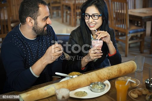 Indoor shoot of multiethnic Asian, young couple drinking strawberry milk shake and eating south Indian cuisine that is paper dosa, sambhaar and chutney at an Indian restaurant. Two people, waist up, selective focus and horizontal composition with copy space.
