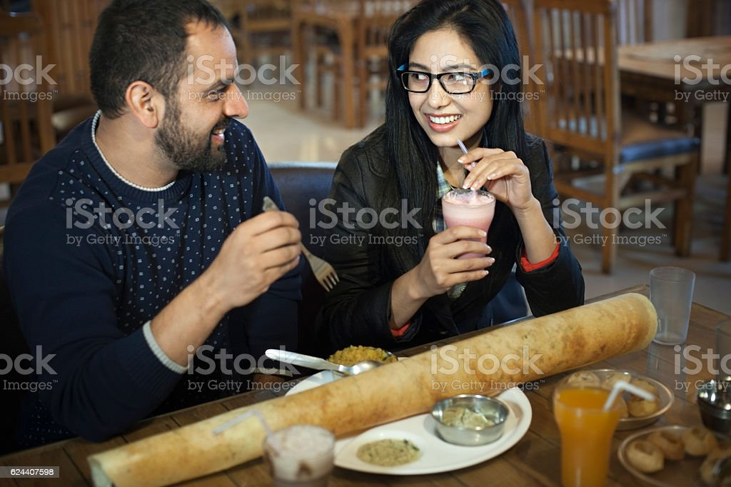 Multi ethnic young couple eating south Indian food at restaurant. stock photo