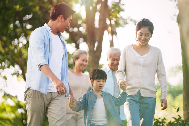 multi generation asian family relaxing outdoors in park stock photo