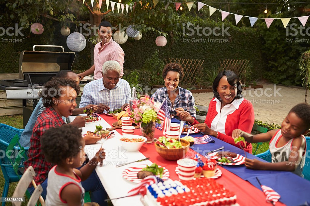 Multi generation black family at table for 4th July barbecue stock photo