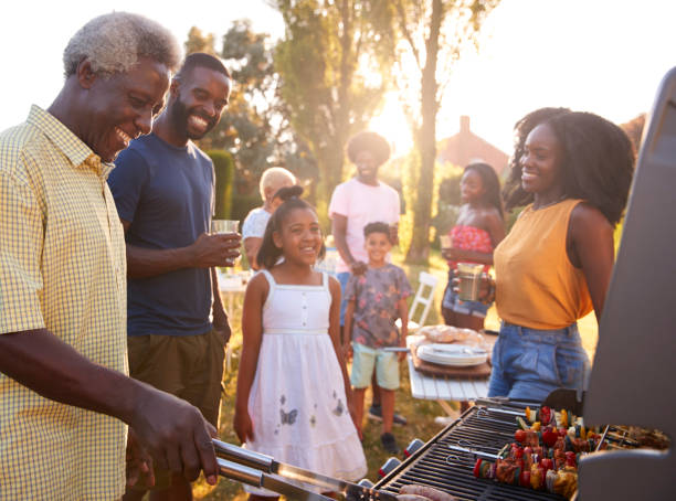 multi generation black family barbecue, grandad grilling - жареный на гриле стоковые фото и изображения