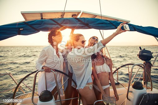 Group of different aged women having a party and making a selfie with mobile phone while sailing on sailboat at sunset. They are very happy and cheerful.