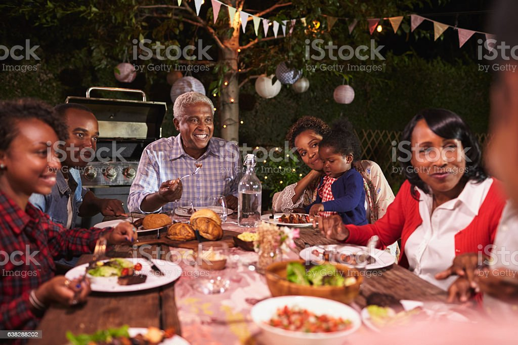 Multi generation family eating dinner in garden, close up stock photo
