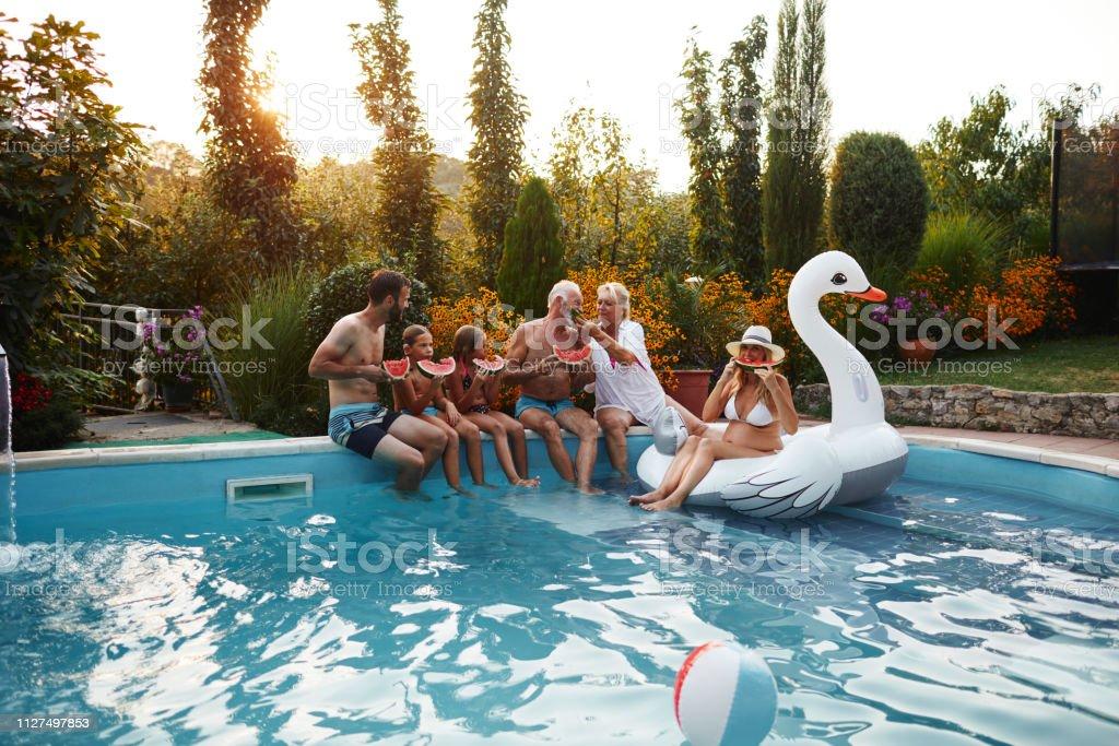 Multi generation family enjoy watermelon on poolside. Boy has...