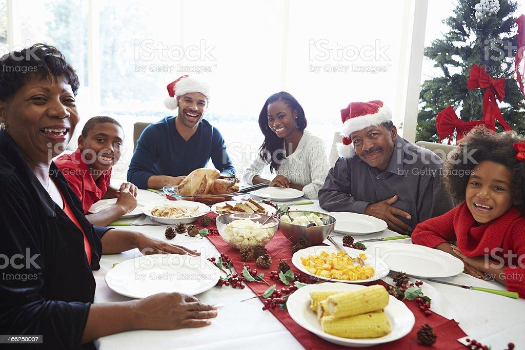 Multi Generation Family Enjoying Christmas Meal At Home Smiling At...
